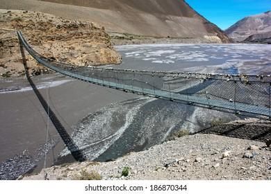 rope hanging suspension bridge above Kali Gandaki Nadi River between Annapurna and Dhaulagiri himal in Nepal