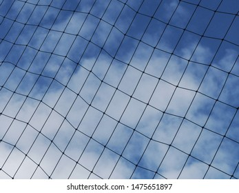 Rope mesh for blocking the edge of the field, braided nylon rope into a square mesh, with blue sky as a background.