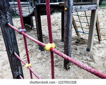 Rope nets and wooden hanging bridge  in children's playground, sand on the ground