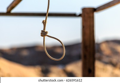 Rope noose hanging outdoors in sandy wilderness on sunny blue sky background. Scaffold for committing death punishment executions or suicide abstract idea. Judgement and justice