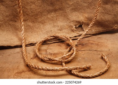 The rope on the background of burlap and wooden board