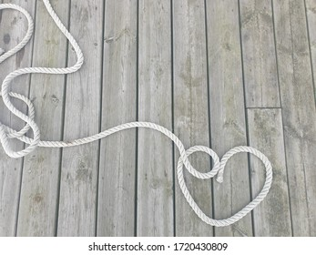 A rope on a dock in a shape of a heart. Abstract art background.
