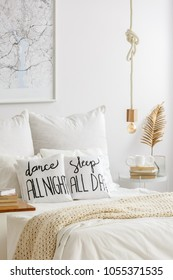 Rope pendant light above a cozy bed with quote print pillows and a side table with books and golden decoration in a white stylish home interior