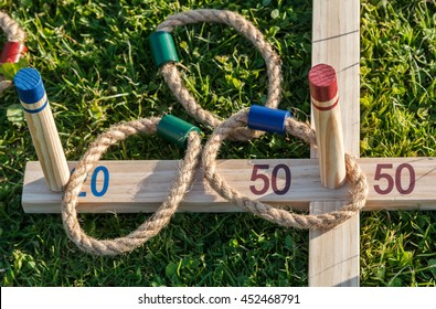 Rope quoit rings on wooden pegs on the traditional garden game.  One hoop is over the 50 points peg - the bulls eye.