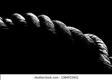 Rope from a sailing boat, black and white at high contrast, low key style, close-up. Shallow depth of field. SDF
