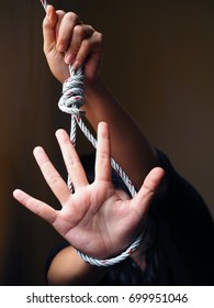 Rope slipknot with woman showing STOP hand, suicide concept