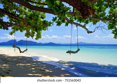 Rope swings on the beach at Koh Kradan in the Andaman Sea with Koh Muk in the background