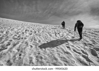 A Rope Team of Mountaineers Climbs Towards the Summit