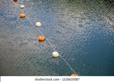 Rope with white and yellow restriction markers on water surface for prohibiting of swimming in deep lake or sea.