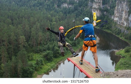 Ropejumping: Young man, tethered to a safety rope, jumping from a great height into a canyon above the river, panorama.
