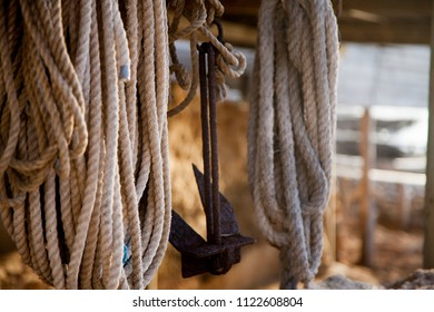 Ropes and an anchor on a small, old wooden jetty in the Mediterranean Sea