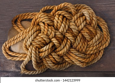 Ropes jute tackle knots on brown wooden background texture