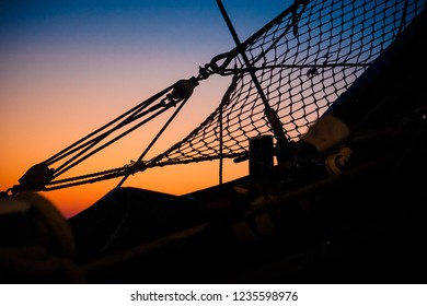 Ropes, nets, cables, pulleys and bollards as shadows against a colorful sky of red and blue colors of the sunset. Hitorical details of an old ship in the harbor
