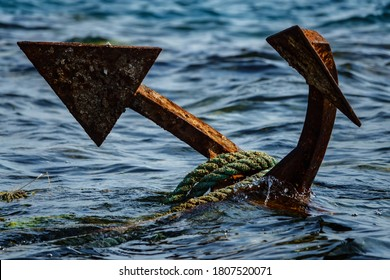 Rope-wrapped rusty anchor in the sea