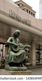 Roppongi crossing, Roppongi, Tokyo/ Japan - May 2016: Statue of 'Kanaderu Otome' (A Girl Playing Guitar) on a sidewalk.  The symbol of peace and restoration by artist Shin Hongo