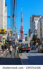 Roppongi, Tokyo - October 28 2014: Pedestrian view of the Tokyo Tower from afar in a Roppongi street. Commuters, taxi, ordinary work day