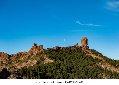 Roque Nublo, symbolic natural monument of Gran Canaria, Canary Islands. Summer sunny day with blue skies and moon and cloud sky. Emblematic volcanic rock formations in mountains of Gran Canaria Spain.