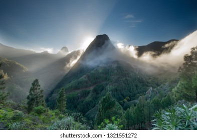 Roque Zarcita seen from the trail to La Laja towards El Cedro during sunset, with clounds falling slowly down the valley and Roque de Agando in the background,Garajonay National Park, La Gomera, Spain