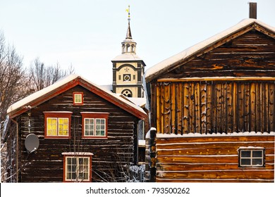 ROROS, NORWAY - DEC 27, 2017: Old wooden houses and the beatiful church tower in the background, satelite dish visible. UNESCO town