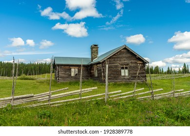 Rorvattnet, Sweden, 02-07-2020. Summer view of an old hill farm in the Swedish highlands. Skewed and warped timbered building and old wooden fences surrounded by green fields