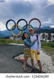Rosa Khutor, Sochi, Russia, June 2018: Roza Khutor, ski resort, Krasnaya Polyana. Happiness tourists couple visiting Olympic village. Young man and woman smiling, take photo. Editorial use only.