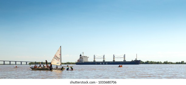 ROSARIO, ARGENTINA - FEBRUARY 17, 2018: Activity on the Parana River. In foreground a lesson of light sailing for kids in a sailboat, a canoe and a bulk carrier ship at the background.
