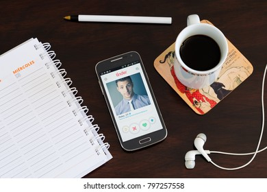 ROSARIO, ARGENTINA - JANUARY 15, 2018: Cell phone over the table with the Tinder application on the screen. A profile of a men its visible. Social network.