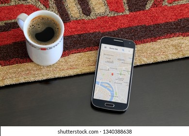 ROSARIO, ARGENTINA - JANUARY 21, 2017: Smartphone over the table with a map of Rome, Italy, on the screen. Aside a coffee cup. GPS Technology. Web page, app.