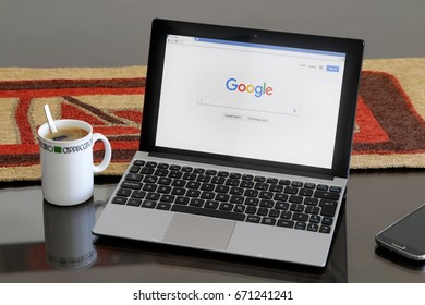 ROSARIO, ARGENTINA - JANUARY 21, 2017: Netbook over table and a coffee cup aside. In the screen of computer is open google searcher page.