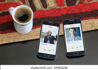 ROSARIO, ARGENTINA - JANUARY 21, 2017: Two cell phones over the table, on the screen of both its open the Tinder application with a profile of a men and a woman respectively. Social network.