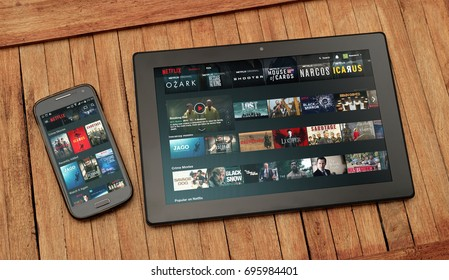 ROSARIO, ARGENTINA - MARCH 27, 2017: Tablet and smartphone over table. The Netflix´s website is open on the screen of both. In these can see thumbnails of movies and serials.