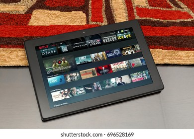 ROSARIO, ARGENTINA - MARCH 27, 2017: Tablet over table. Netflix´s website is open on the screen. In this can see thumbnails of movies and serials.