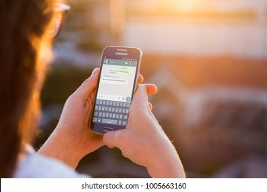 ROSARIO, ARGENTINA - NOVEMBER 8, 2017: Girl with smartphone in her hands and a whatsapp conversation on the screen. Young woman, millennial, chatting. Technology. Communications.