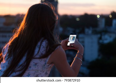 ROSARIO, ARGENTINA - NOVEMBER 8, 2017: Woman at the sunset with a cell phone in her hands. On the screen you can see the Tinder application with a man profile open. Application. Social network.