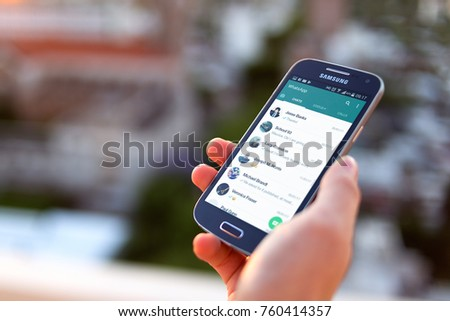 ROSARIO, ARGENTINA - NOVEMBER 8, 2017: Young woman with cell phone in her hand. On the screen you can see the Whatsapp application with the contact list open.