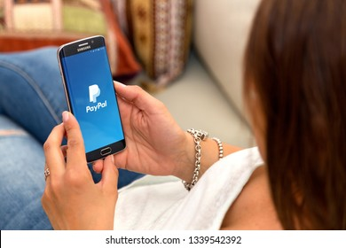 ROSARIO, ARGENTINA - OCTOBER 28, 2017: Young woman holding a cell phone showing  Paypal logo on screen. PayPal is an online electronic payment system. Smartphone application.