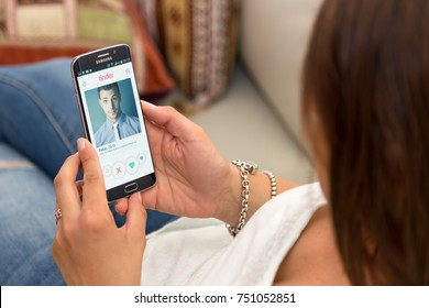 ROSARIO, ARGENTINA - OCTOBER 28, 2017: One young and single woman at home resting in armchair holding a smartphone with Tinder  application on the screen.