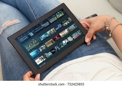 ROSARIO, ARGENTINA - OCTOBER 28, 2017: One young woman resting in armchair holding a smartphone with Netflix web open in the screen.