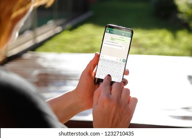 ROSARIO, SANTA FE, ARGENTINA - OCTOBER 7, 2018: Woman with smartphone in her hands and a whatsapp conversation on the screen. Young woman, chatting. Technology. Communications.