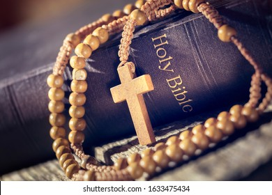 Rosary beads and crucifix cross on holy bible background