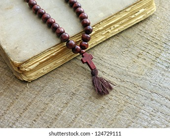 rosary beads and holy bible on wooden background, close-up