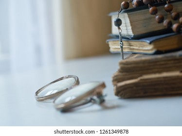 The rosary beads on Catholic Church liturgy books and old glasses on the side of them.