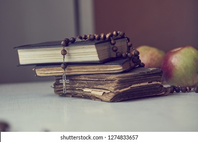 The rosary beads on Catholic Church liturgy books and apples behind them.
