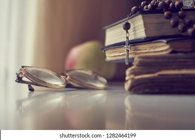 The rosary beads on Catholic Church liturgy books and old glasses and ripe apple on the side of them.