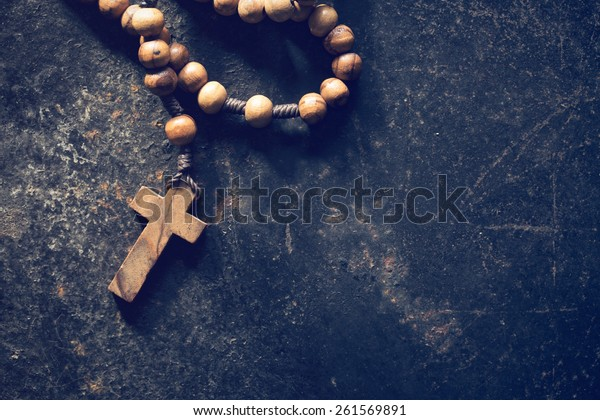 rosary beads on old black background