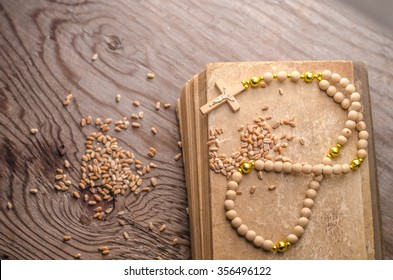 rosary beads on a vintage old books,grain wheat,horizontal photo