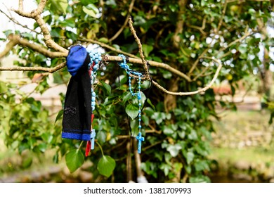 Rosary beads and a sock tied to a tree at an Irish holy well shrine.