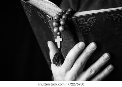 Rosary, cross and Bible  in female hands on a dark background. Holy book.  Black and white photography