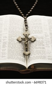 Rosary with crucifix lying on open Bible.