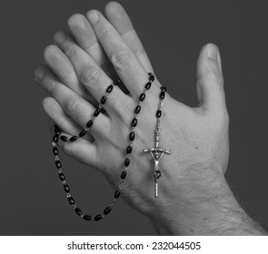 Rosary dangling from a man's hand